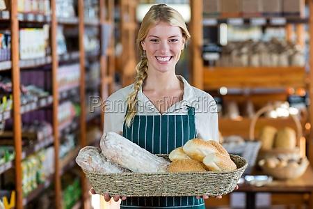 smiling female staff holding basket of