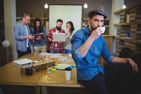 stylish businessman drinking coffee while sitting