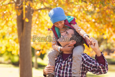 cheerful father carrying son on shoulder