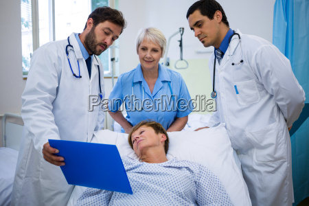 doctors showing medical report to patient