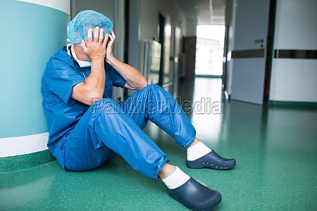 sad surgeon sitting on floor in