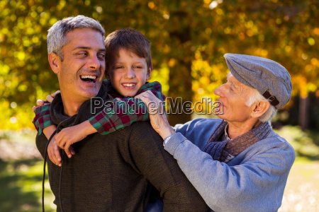 happy man piggybacking son while with
