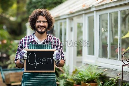gardener holding open sign placard outside