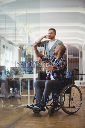 handicap businessman and colleague sticking adhesive