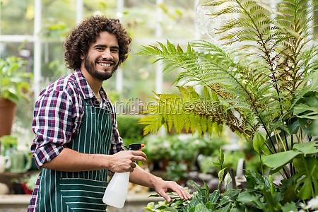 happy male gardener watering plants