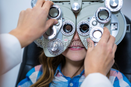 female optometrist examining young patient on