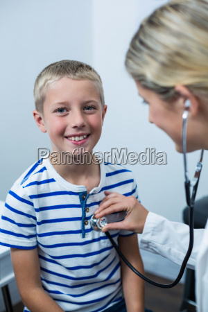 female doctor examining young patient with