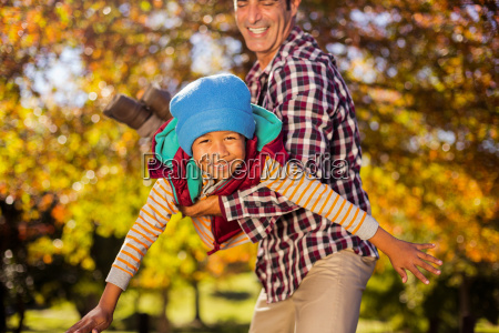 playful father holding son at park