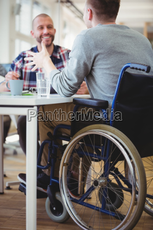 happy handicap businessman discussing with colleague