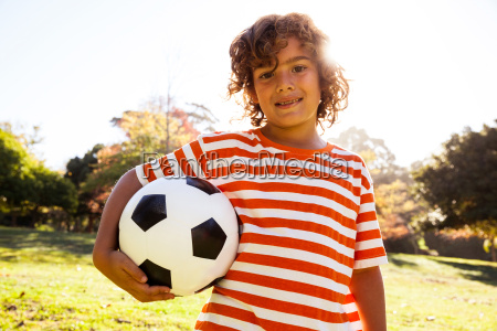 portrait of smiling boy holding soccer