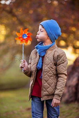 boy blowing pinwheel at park