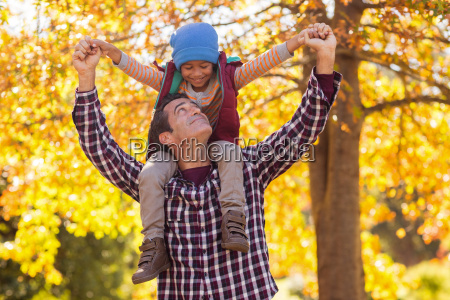 father carrying son on shoulder at