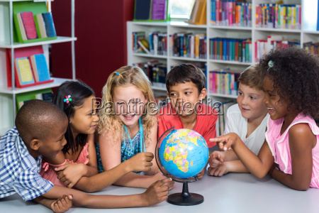 kinder mit globus auf tisch