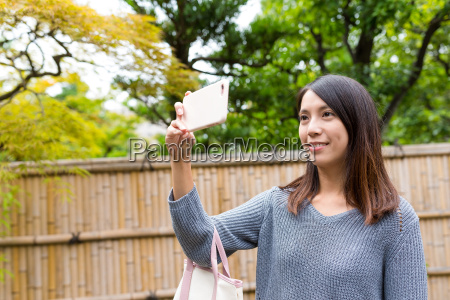woman taking photo by cellphone at