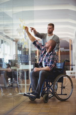 handicap businessman with colleague sticking adhesive