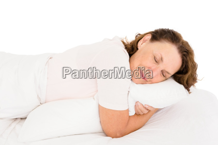 mature woman hugging pillow while sleeping