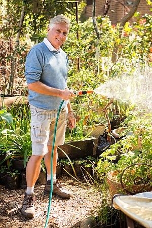 portrait of gardener watering plants from