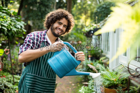 confident male gardener watering potted plants