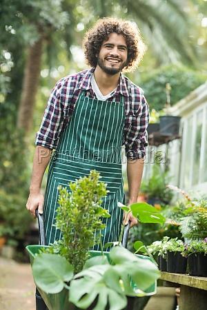 happy male gardener carrying plants in