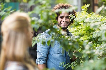 male gardener looking at woman standing