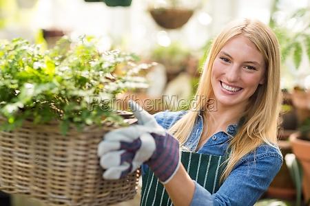 young gardener holding plants in wicker