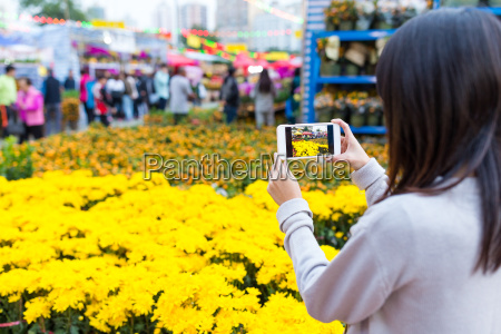 woman taking photo with cellphone on