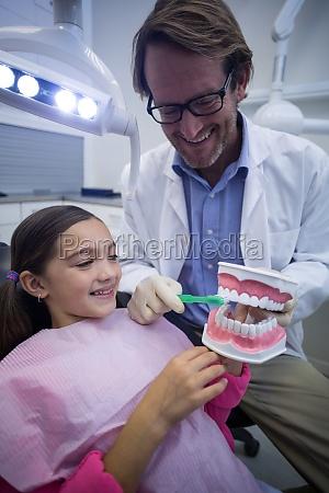 zahnarzt zeigt jungen patienten wie man