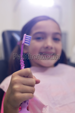 junge patientin haelt ihre zahnbuerste