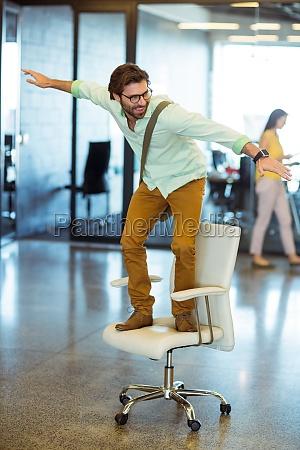 maennlicher unternehmensleiter der auf stuhl steht