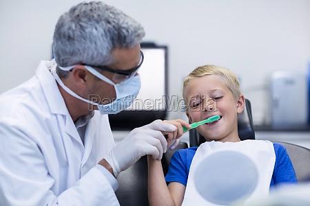 zahnarzt putzt jungen patienten zaehne