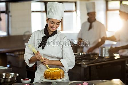 weiblicher chef rohr sahnehaeubchen auf kuchen