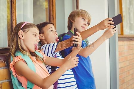 schulkinder selfie mit handy in gang