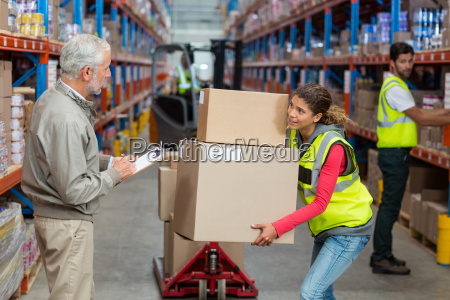 worker holding cardboard boxes looking her