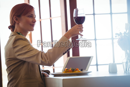 woman holding a red wine
