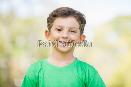young boy smiling in park
