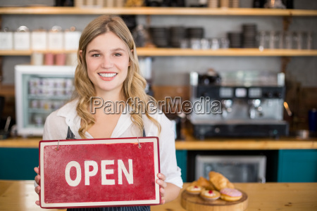smiling waitress showing signboard with open