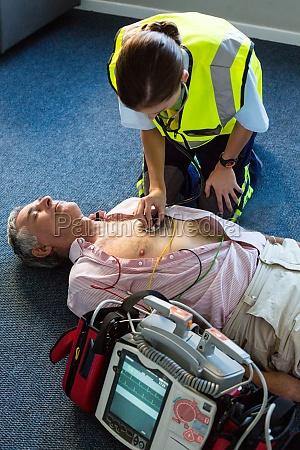 sanitaeter untersucht einen patienten waehrend der