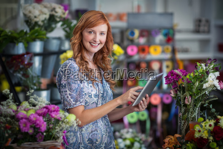 smiling female florist using digital tablet