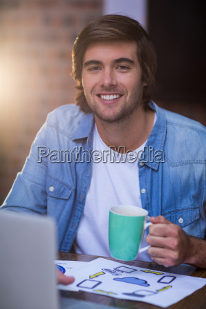 young businessman having coffee in office