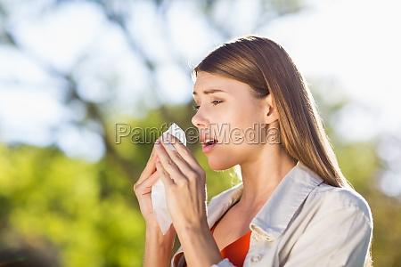 schoene frau mit gewebe beim niesen