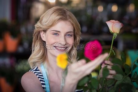 smiling female florist arranging flower bouquet