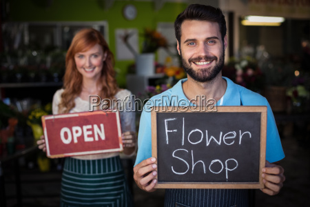man holding slate with flower shop
