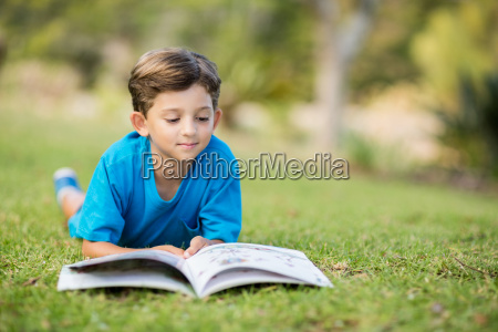young boy reading book in park