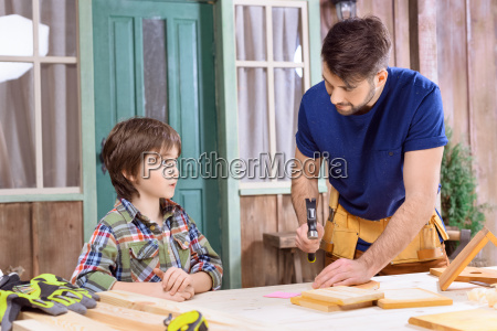 portrait of father teaching concentrated son