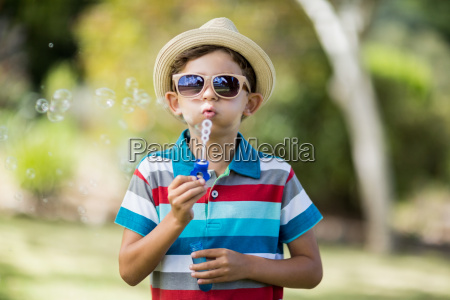 young boy in sunglasses blowing bubbles