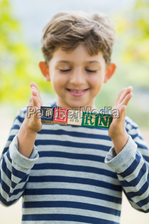 boy holding blocks in park which