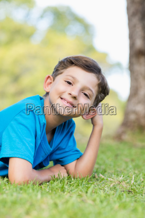 smiling young boy lying on grass