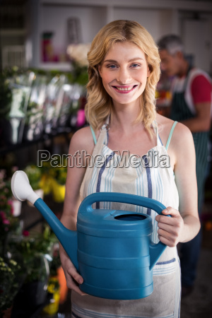 smiling female florist holding watering can