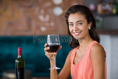 smiling woman holding glass of red