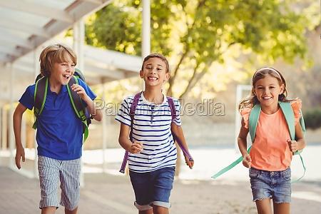 glueckliche schule kinder laufen im korridor